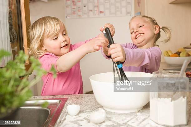 Girl mixing batter in bowl, smiling