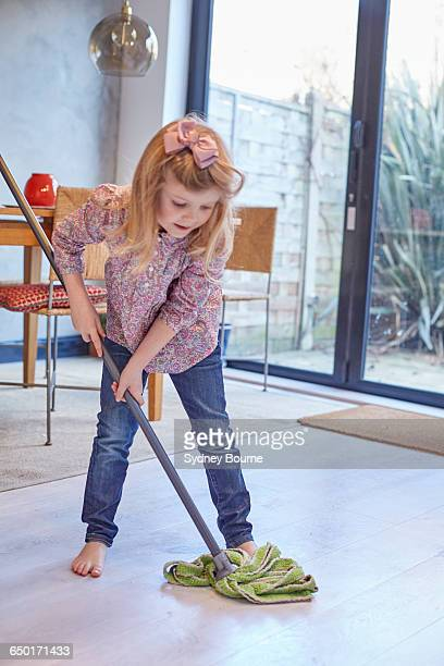Girl mopping dining room floor