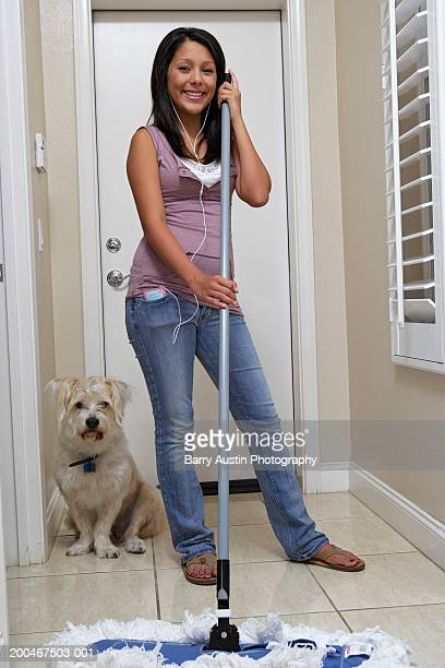 girl (13-15) mopping tiled floor, smiling, portrait - girl wear jeans and flip flops stock photos and pictures
