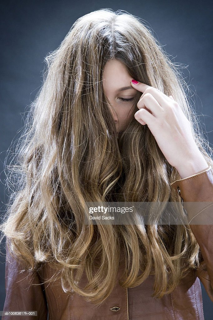 Girl (12-13) moving away hair from face : Stock Photo