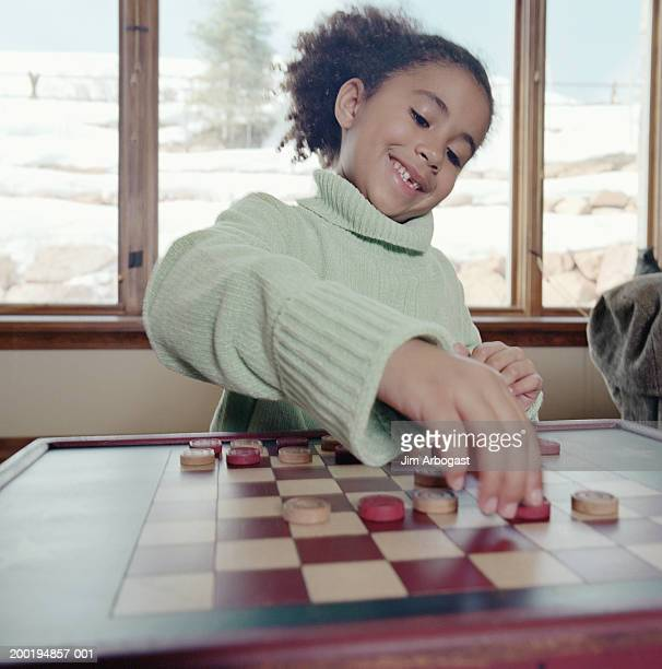 Girl (6-8) moving piece on draught board, smiling