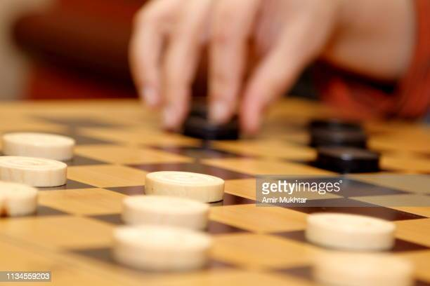 girl moving token on checkers game - chequers stock photos and pictures