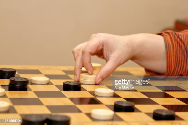 girl moving token on checkers game - chequers stock pictures, royalty-free photos & images