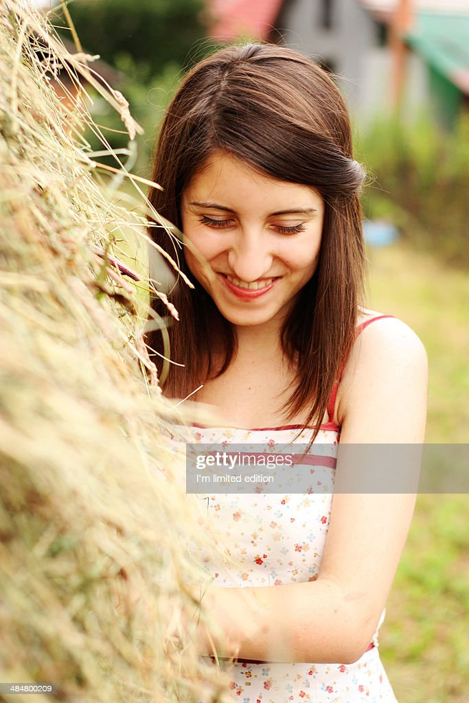 Girl near a stack of hay smiling : Photo