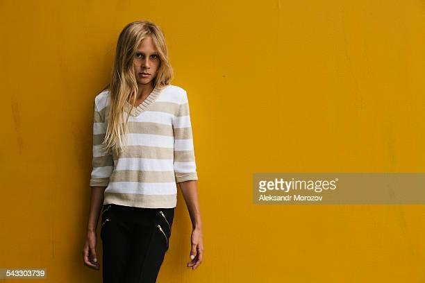 Girl near yellow wall