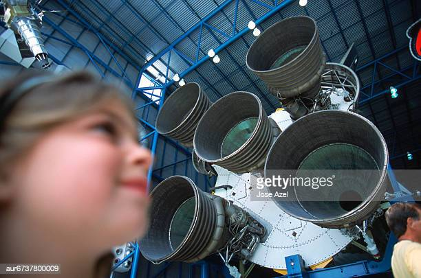 Girl next to Rocket Engines, Cape Canaveral, Kennedy Space Center, Florida, USA.