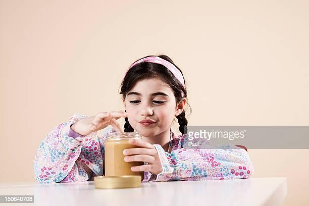 Girl nibbling honey from glass