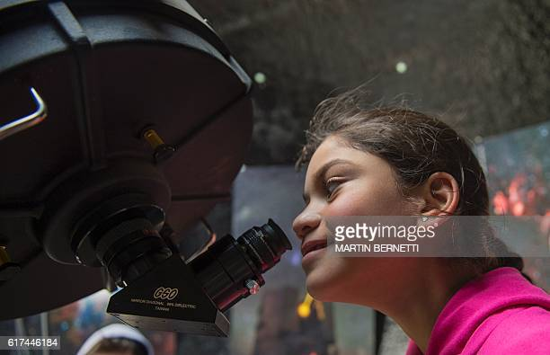 A girl observes the sky through a telescope during a tour at the Astronomic Center 'Cielos Chilenos ' in Colina some 20 kilometres North of Santiago...