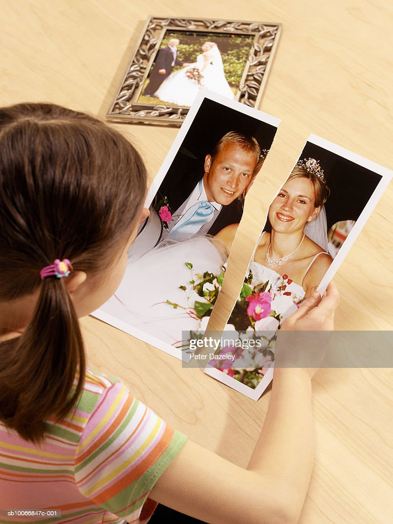 Girl (6-7) observing torn photograph of separated parents wedding : Stock Photo