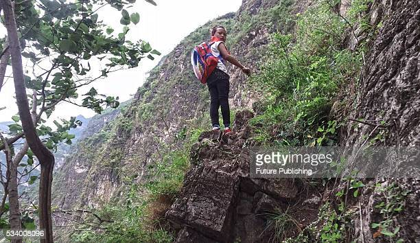 A girl of Atule'er Village looks back during climbing a cliff on her way home in Zhaojue county in southwest China's Sichuan province on May 14 2016...