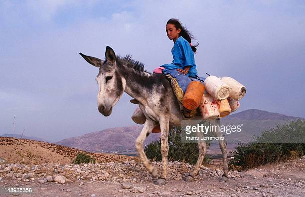 Girl of Berber tribe on donkey transporting water.