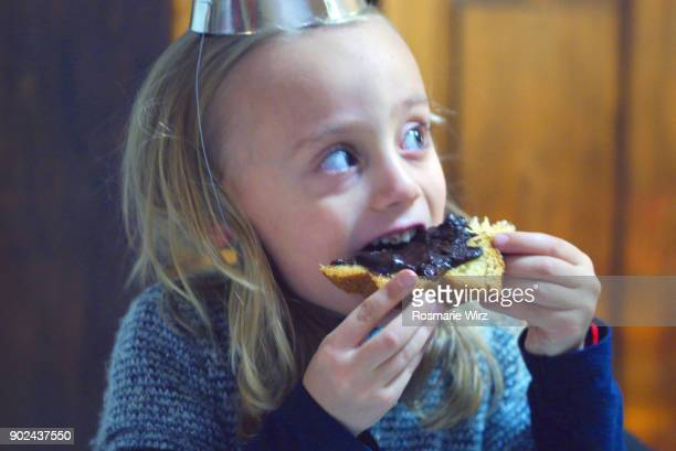 girl of five eating cake with chocolate topping. - seitenblick stock-fotos und bilder