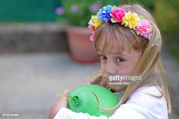 Girl of five holding green balloon, sulky expression