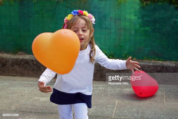 Girl of five playing with orange heart-shaped balloon, smiling