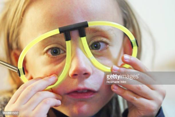 girl of five wearing phosphorescent party fun glasses - phosphorescence stock pictures, royalty-free photos & images