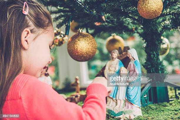 girl of four playing with figurines at nativity scene, europe - nativity stock photos and pictures