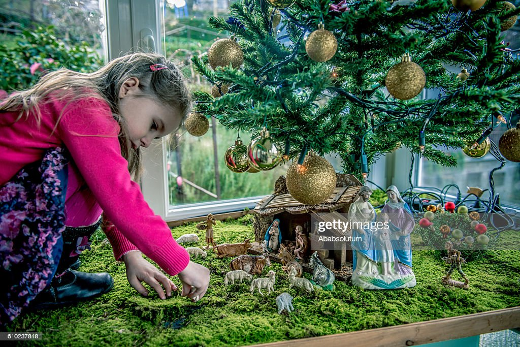 Girl of Four Playing with Figurines at Nativity Scene, Europe : Stock Photo