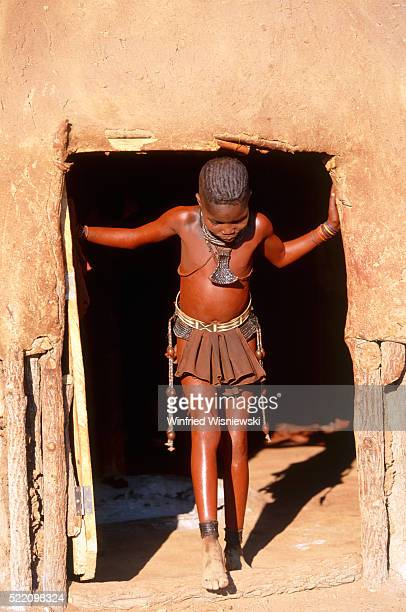 girl of hima tribe standing in door of shack, namibia (near epupa-falls) - himba photos et images de collection