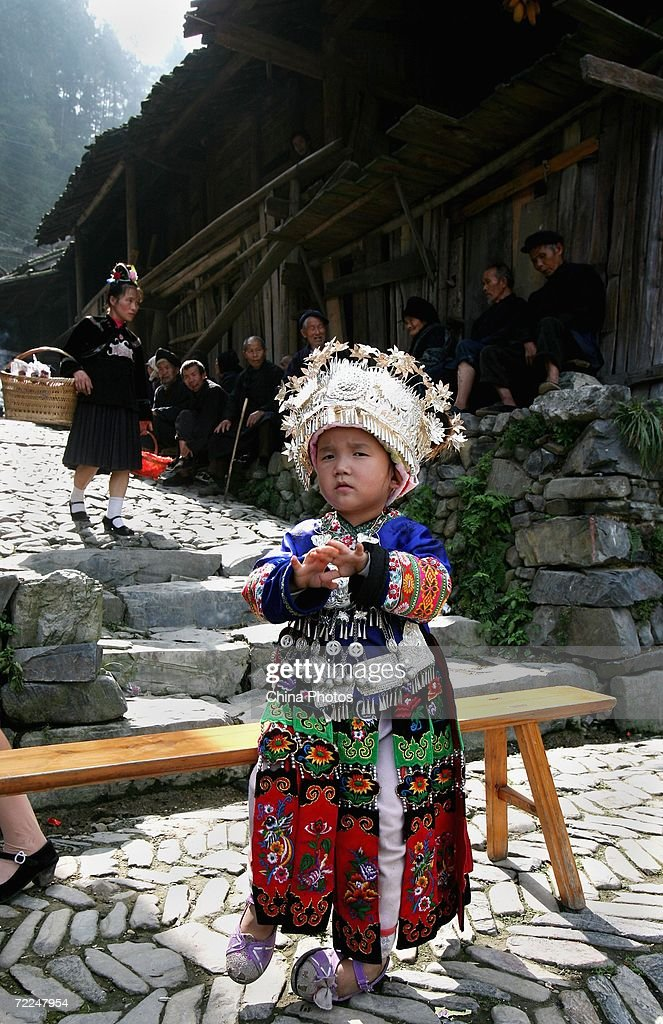 A girl of Miao ethnic origin waits to watch a performance beside a stool at Langdeshang Village on October 21, 2006 in Leishan County of Qiandongnan Miao and Dong Autonomous Prefecture, Guizhou Province, China. With a population of 8,940,116, the Miao people is one of the largest ethnic minorities in southwest China. Qiandongnan Prefecture is a multi-ethnic region where over 20 ethnic minority groups reside. Miao and Dong minorities make up over 70 percent of its population.
