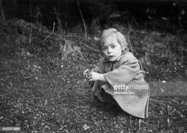 girl of three picking spring flowers. switzerland march 1947. - 1947 stock pictures, royalty-free photos & images