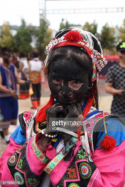 Girl of Yi ethnic group is daubed rice ash on face during the Face Painting Festival in Puzhehei Resort of Qiubei County on July 18, 2016 in Wenshan...