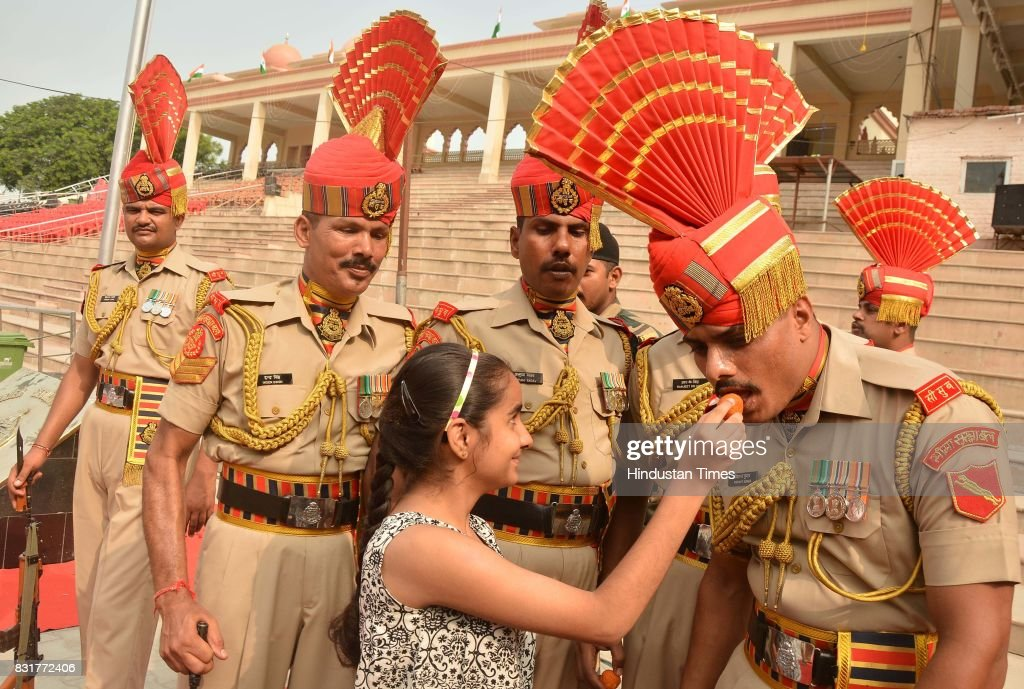 A girl offers sweets to Indian Border Security Force soldiers as they celebrate India's 71st Independence Day at the IndiaPakistan Wagah Border po