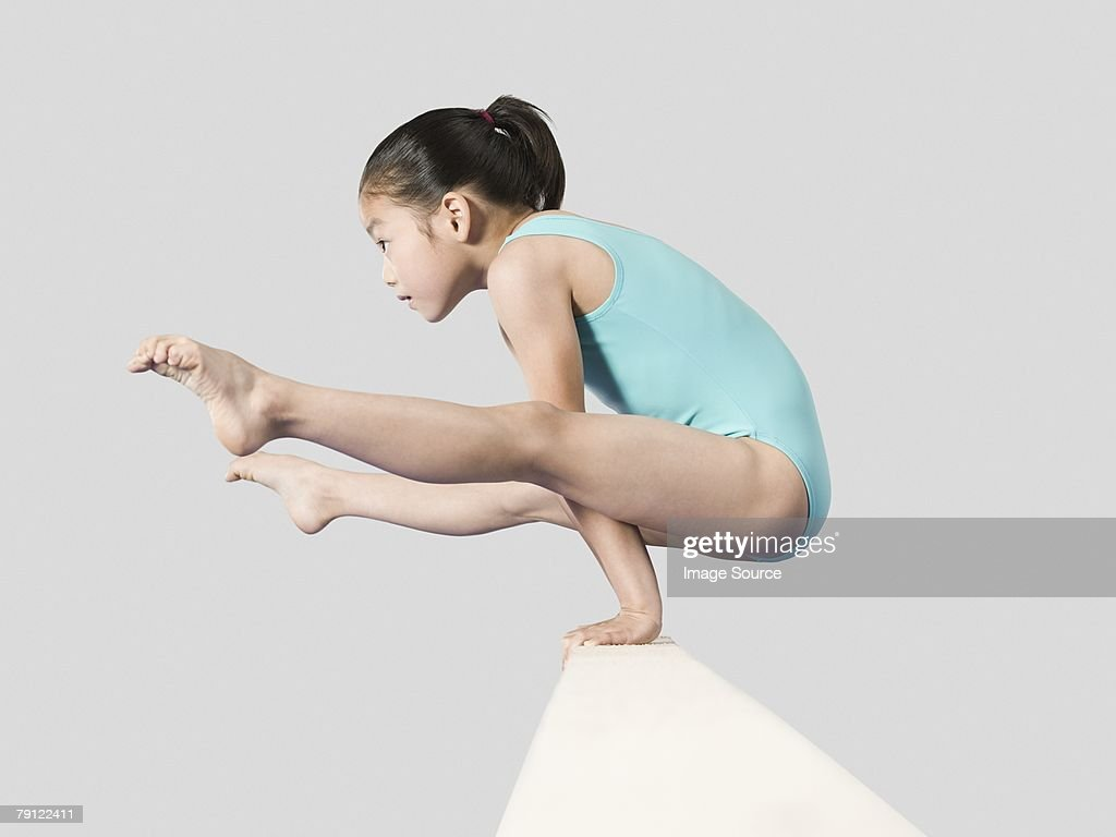 Girl on a balance beam : Stock Photo