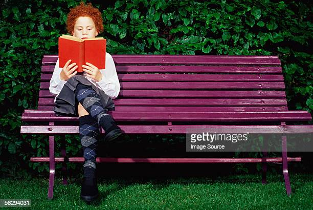 Girl on a bench reading a book