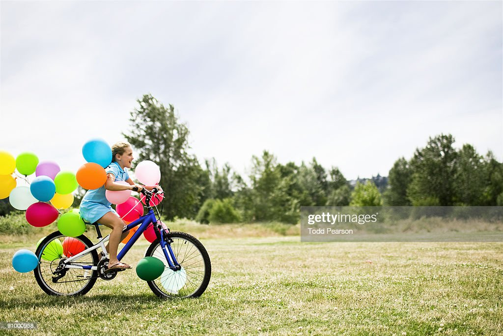 Girl on a Bike with Balloons : Stock Photo