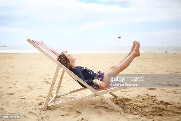 a girl on a deckchair on the beach - zurücklehnen stock-fotos und bilder