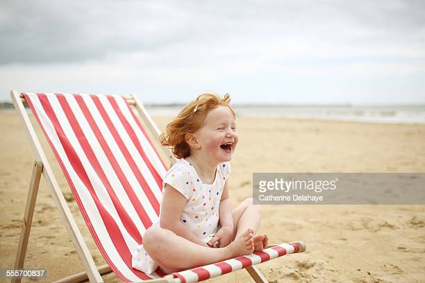 A girl on a deckchair on the beach