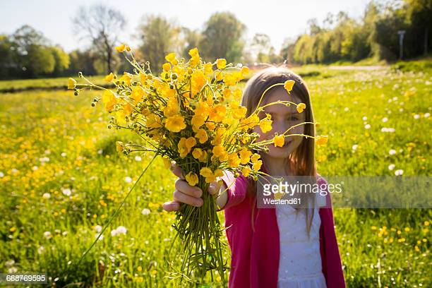 Girl on a meadow gifting bunch of buttercups to viewer