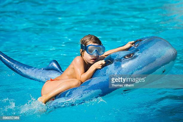 Girl on a ray beach toy in the pool