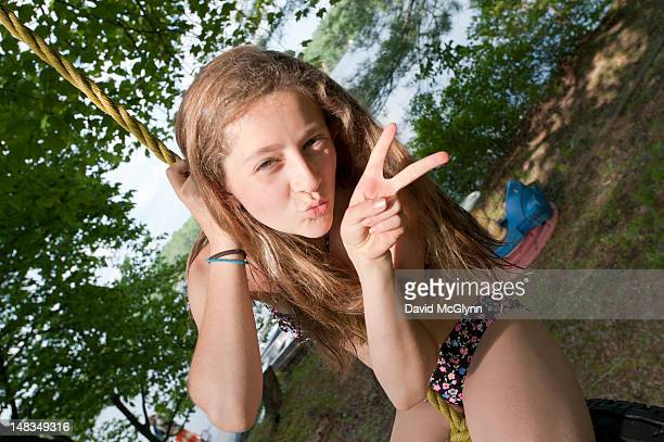 Girl  on a rope swing flashing a peace sign