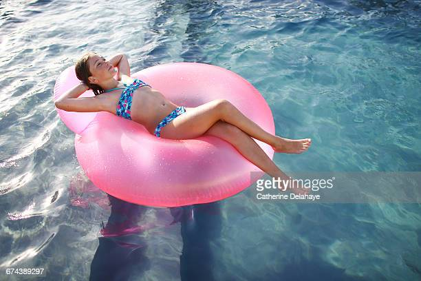 a girl on a rubber ring in a swimming pool - girls sunbathing stock pictures, royalty-free photos & images