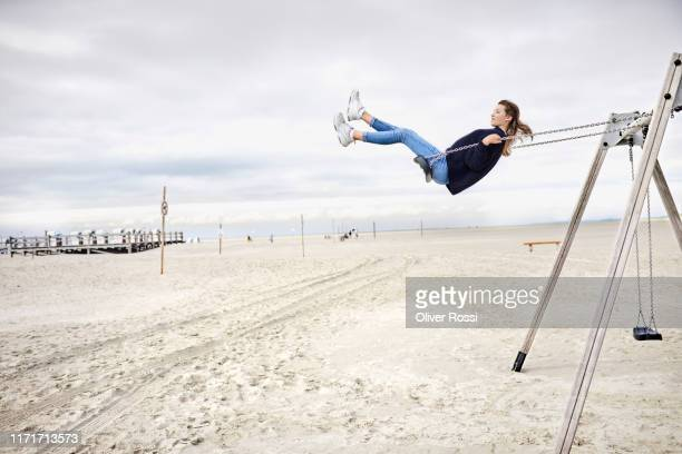 girl on a swing on the beach - effortless stock pictures, royalty-free photos & images