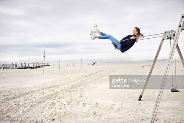 girl on a swing on the beach - schleswig holstein stock-fotos und bilder