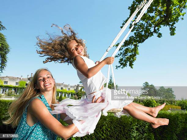 Girl on a swing, pushed by her sister