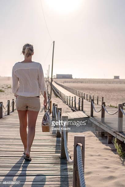girl on a wooden beach catwalk