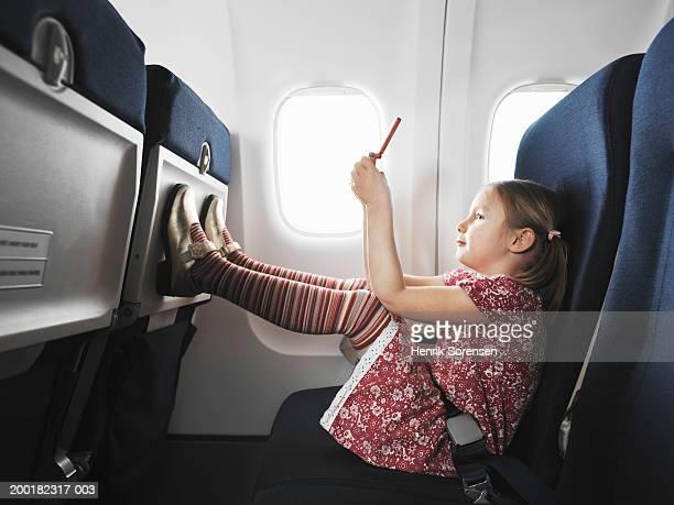 Girl (5-7) on aeroplane using handheld electronic device