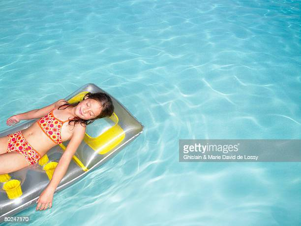 Girl on air mattress in pool.