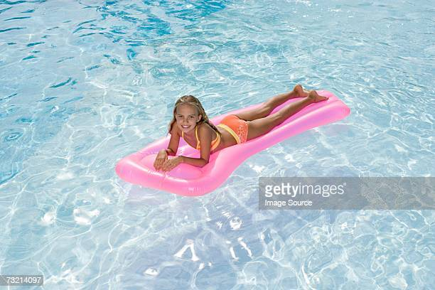 girl on an inflatable mattress - girls sunbathing stock photos and pictures