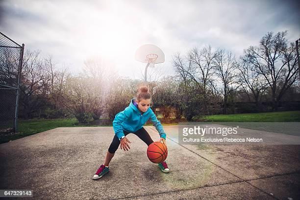 Girl on basketball court bouncing basketball