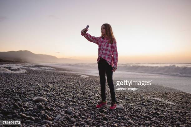 Girl on beach at sunset taking photos
