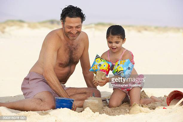 girl (2-4) on beach building sandcastles with father - female hairy chest stock pictures, royalty-free photos & images