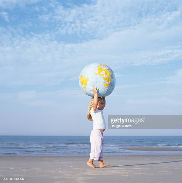 Girl (2-4) on beach  carrying inflatable globe on head, side view