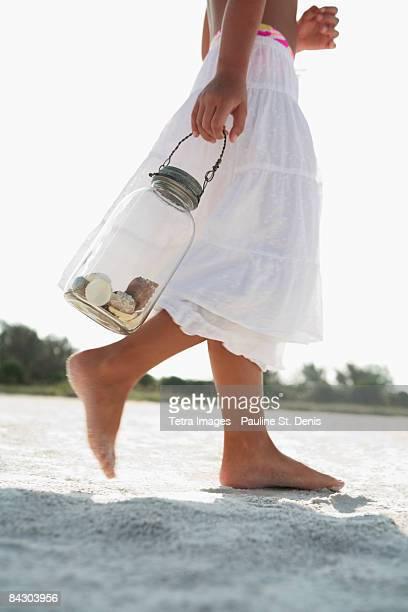 Girl on beach carrying jar of shells