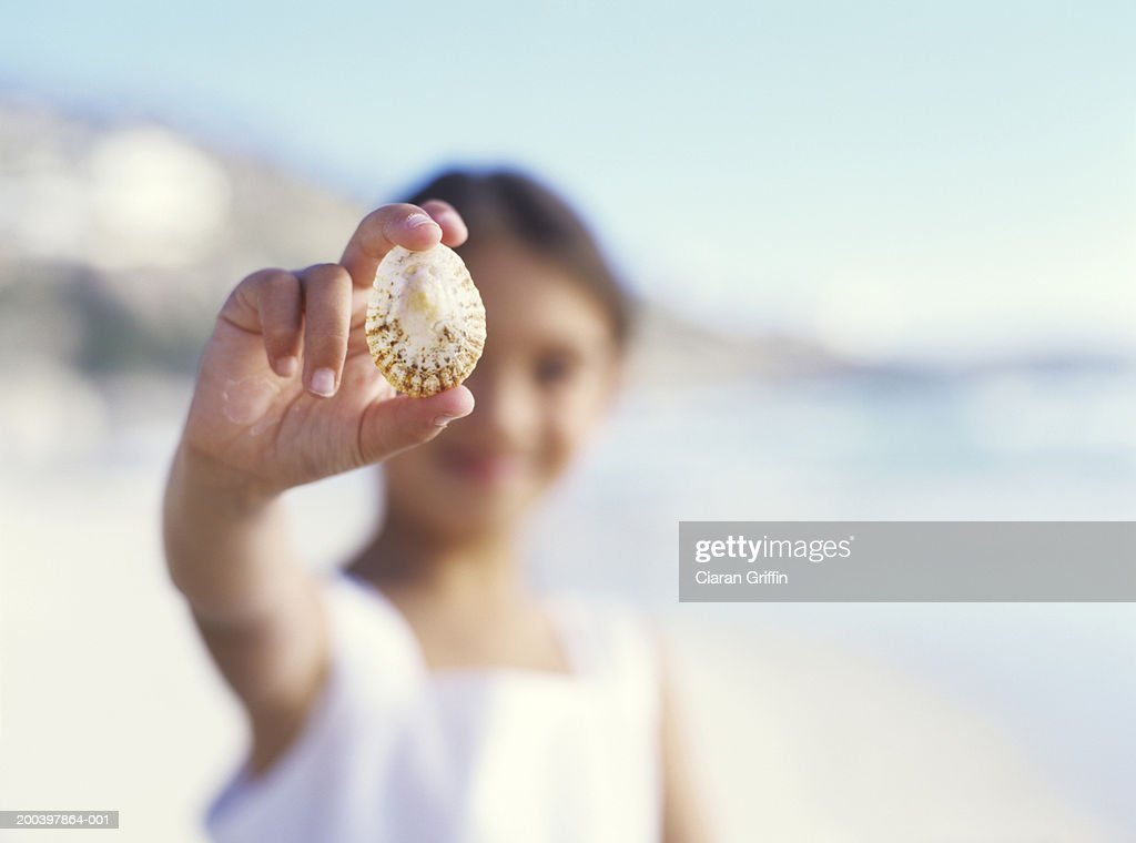 Girl (5-7) on beach holding shell, close up, portrait : Stock Photo
