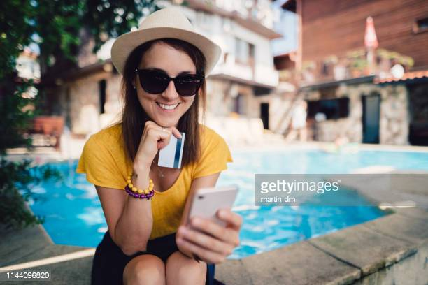 girl on beach holiday making hotel reservation online - credit card purchase stock pictures, royalty-free photos & images