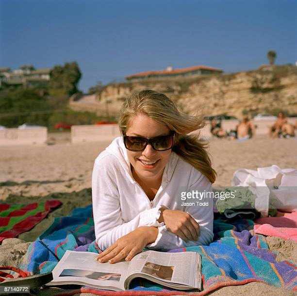 girl on beach reading magazine - jason todd stock photos and pictures